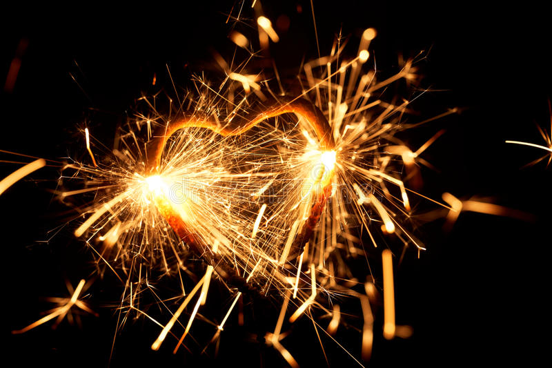 Burning sparkler in form of a heart. Macro photo of a burning sparkler in form of a heart stock images