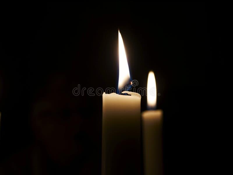 burning stearinljus mörker arkivfoto