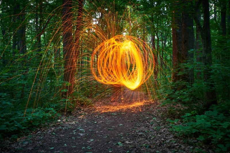 Burning steel wool spinned in the forest. Showers of glowing sparks from spinning steel wool royalty free stock photography