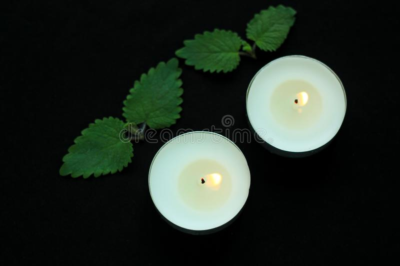 White burning tealight candles on black background. Beauty, SPA treatments, massage therapy and relax concept royalty free stock images