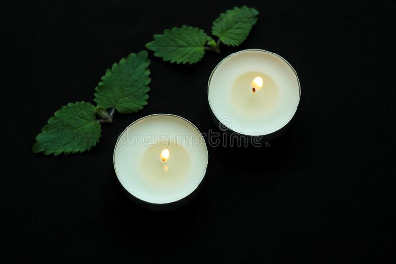 White burning tealight candles on black background. Beauty, SPA treatments, massage therapy and relax concept stock image
