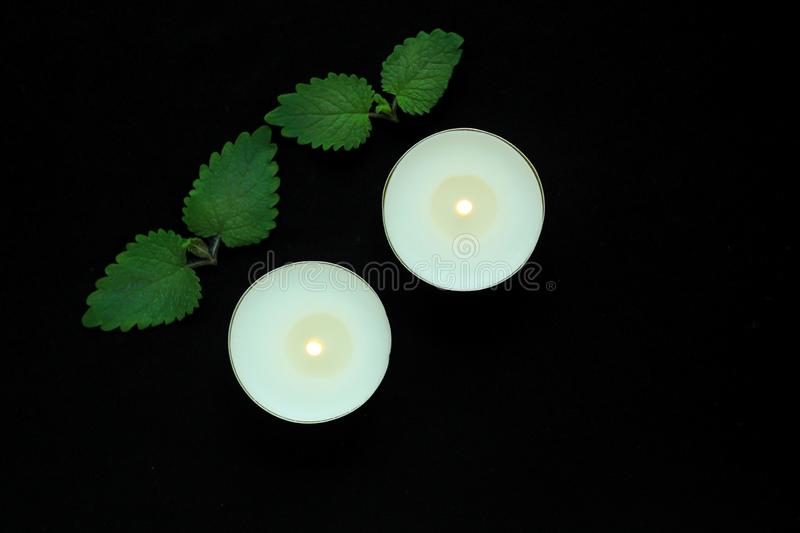 White burning tealight candles on black background. Beauty, SPA treatments, massage therapy and relax concept royalty free stock photography