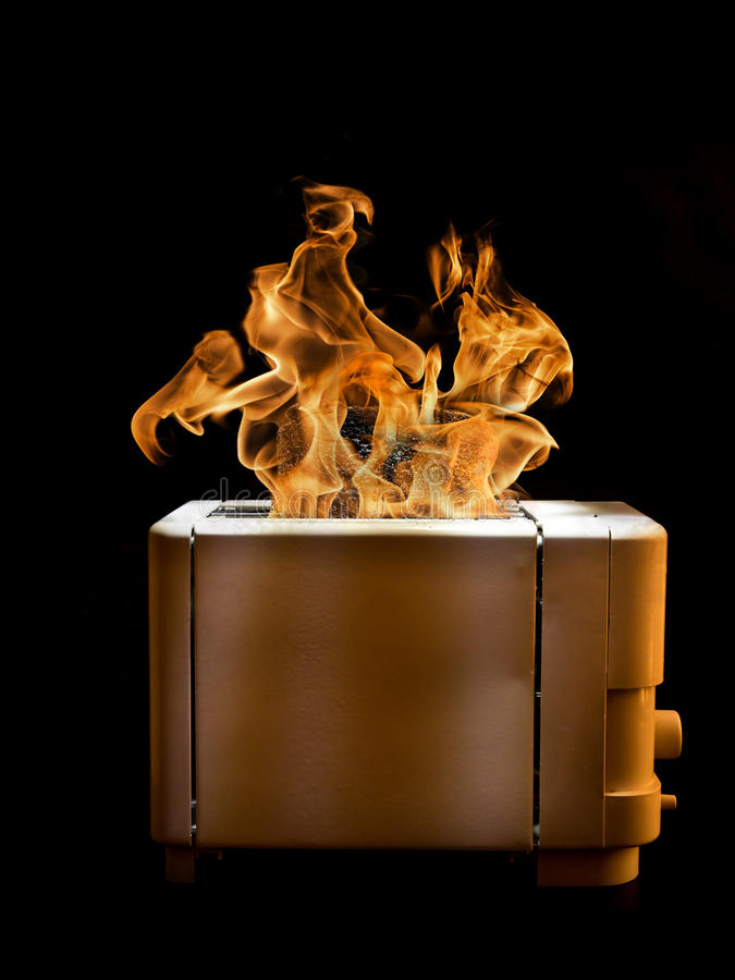 Burning toaster. Toaster with two slices of toast caught on fire over black background stock images