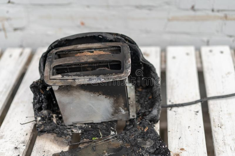 Burning toaster. Toaster with two slices of toast caught on fire over white background stock images