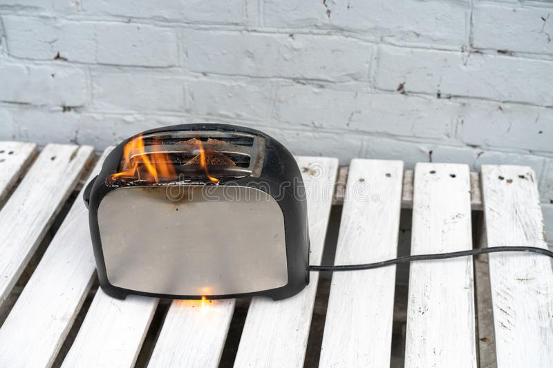 Burning toaster. Toaster with two slices of toast caught on fire over white background stock image