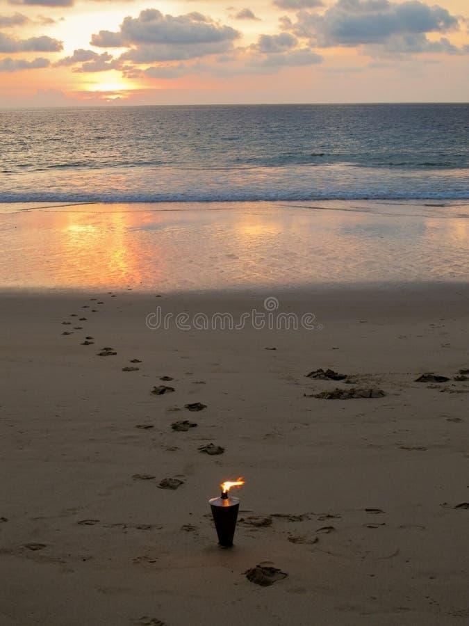 Burning torch on romantic sunset beach royalty free stock photos