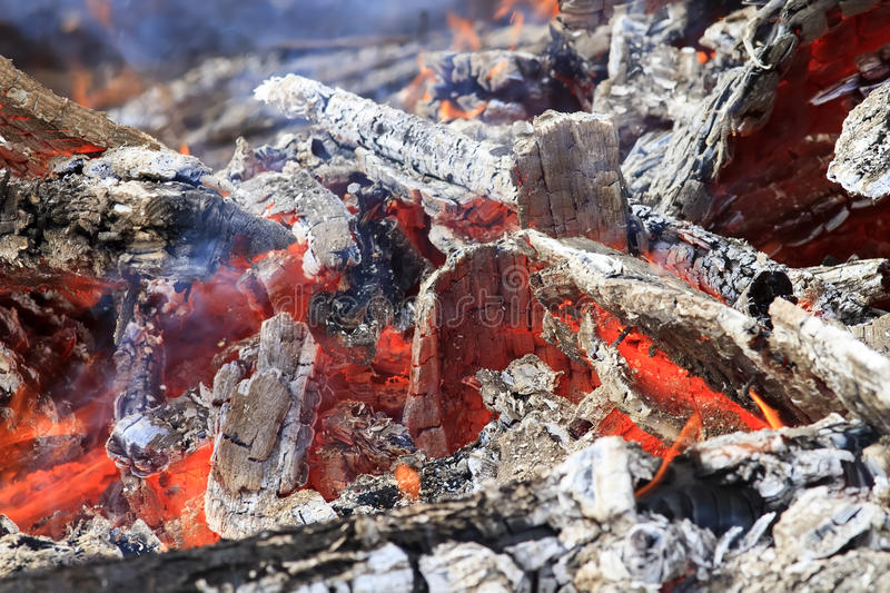 Burning up white hot coals and the bright red flames royalty free stock photo