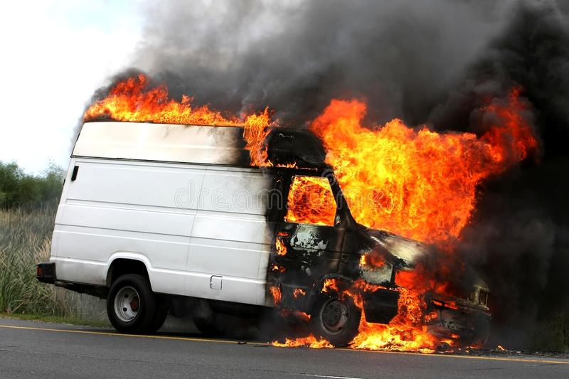 Burning Vehicle. Delivery type vehicle on side of road burning with large flames and smoke stock photos