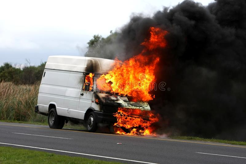Burning Vehicle Disastor. Delivery type vehicle on side of road burning with large flames and smoke stock photography