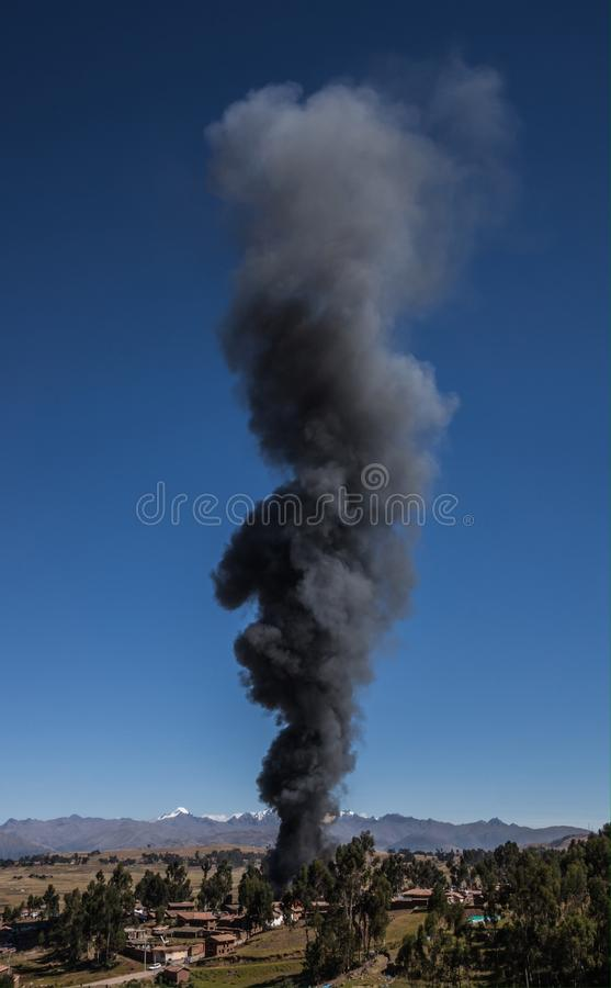 Burning Village. A Burning village causes a big pile of dark, black smoke on a sky blue summer day royalty free stock image
