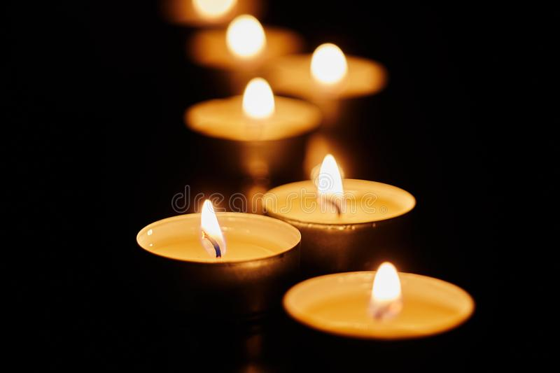 Burning votive candles on dark background stock photo