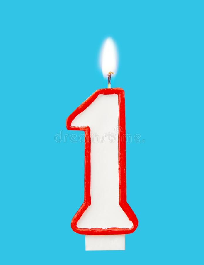 Burning wax candle for a birthday cake in the form of number one. Blue background stock image