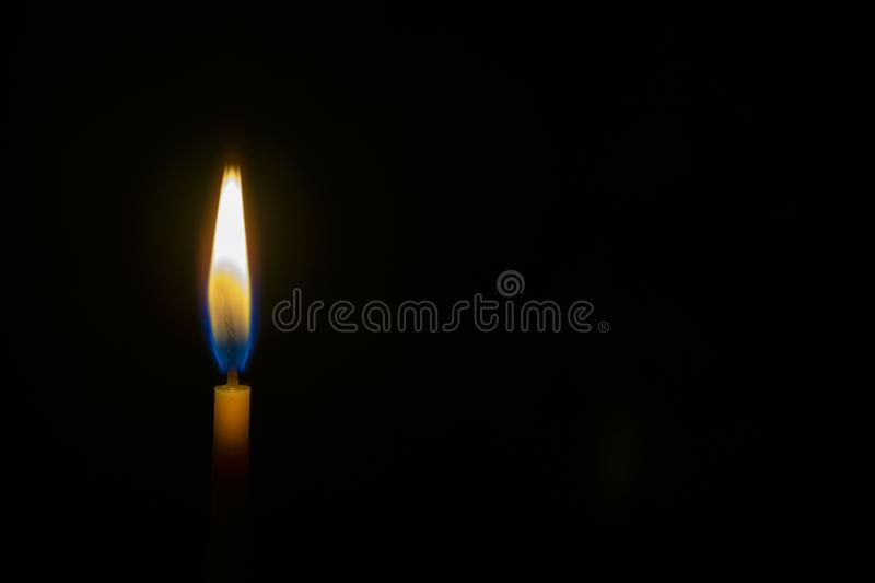 Burning wax candle. On a black background royalty free stock photos