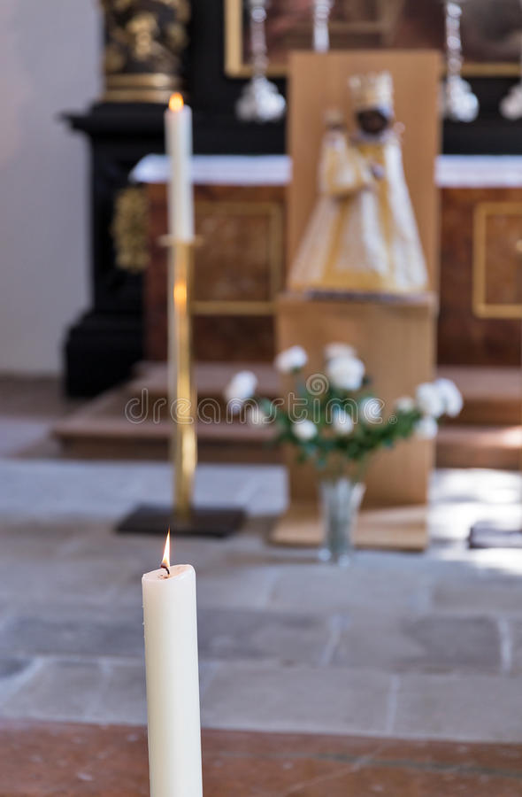 Burning wax candle in cathedral - religion background, focus on foreground. Burning wax candle in cathedral - religion background closeup, focus on foreground royalty free stock images