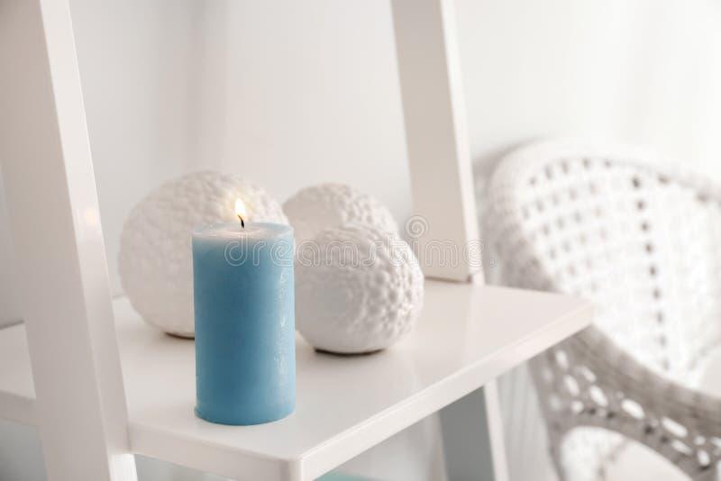Burning wax candle on shelf stock images