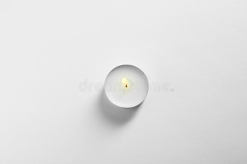 Burning wax candle on white background top view stock images