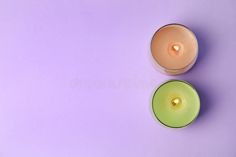 Burning wax candles in glass holders on purple background, flat lay. Space for text royalty free stock photography