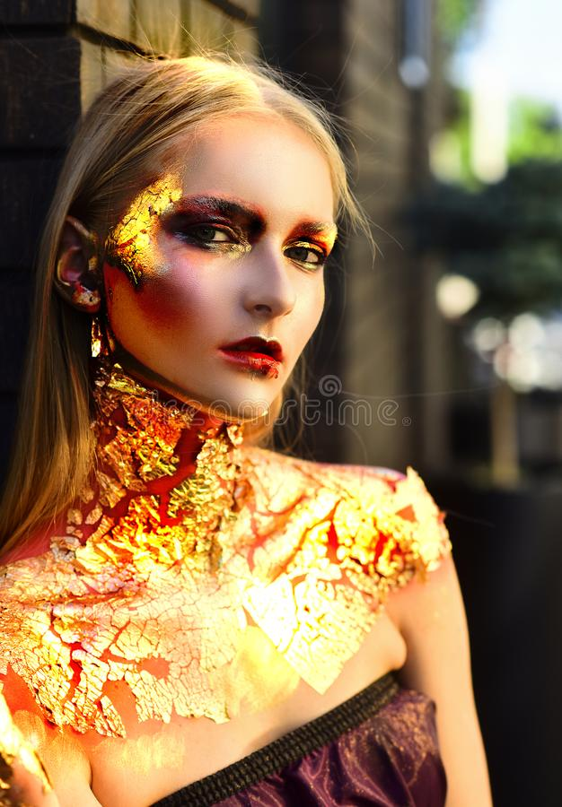 Burning woman golden Halloween face. High Fashion Halloween model woman in golden bright sparkles. Halloween design make stock image