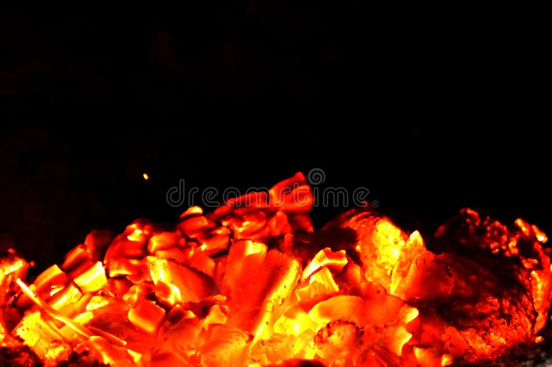 Burning wood coals and one flying spark. Burning wood coals and flying spark in dark fireplace, incandescent  atmosphere stock photos
