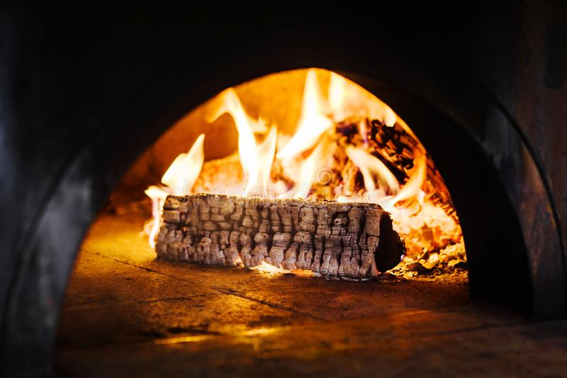 Burning wood in fireplace of traditional brick pizza oven stock photos