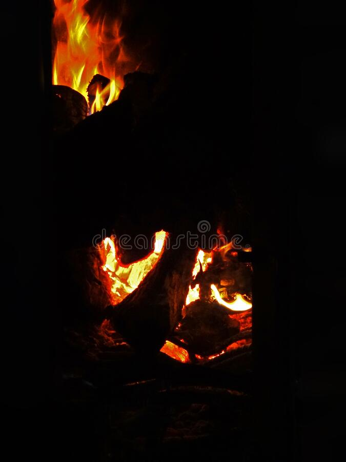 Burning wood in the fireplace which is in the room. Warmth and desire to stay stock photography
