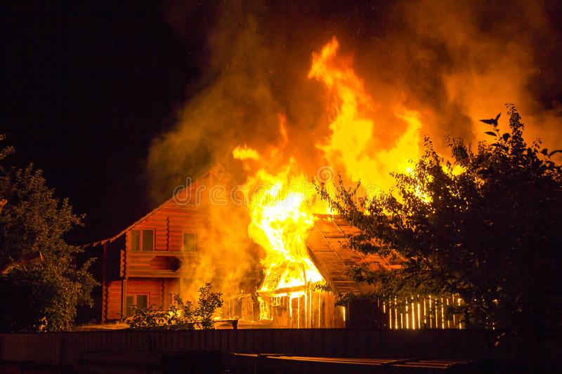 Burning wooden house at night. Bright orange flames and dense sm. Oke from under the tiled roof on dark sky, trees silhouettes and residential neighbor cottage royalty free stock image
