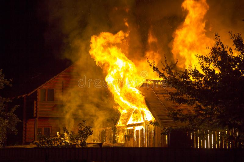 Burning wooden house at night. Bright orange flames and dense smoke from under the tiled roof on dark sky, trees silhouettes and r. Esidential neighbor cottage stock image