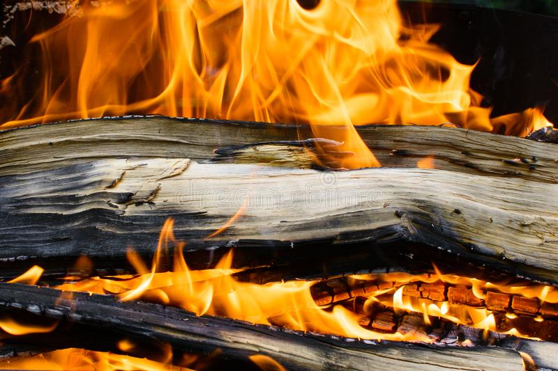 Burning wooden log covered with red fire. Grilled fire in the barbecue. Dangerous for burns. Background with fire and wood stock photography