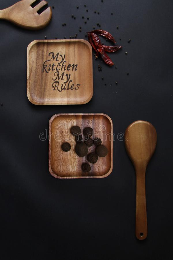 Burning on a wooden plate on a black background garlic and dried paprika stock photos