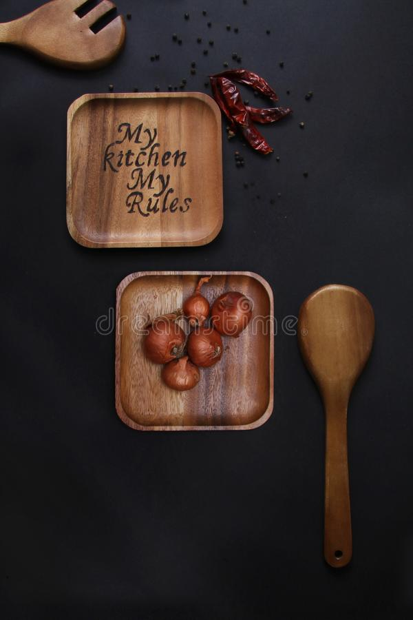 Burning on a wooden plate with a spoon Red Onions on a plate stock photography