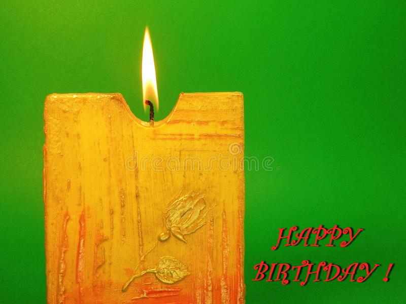 Burning yellow candle - Happy Birthday card. Burning beautiful candle on green background - Happy Birthday card royalty free stock images