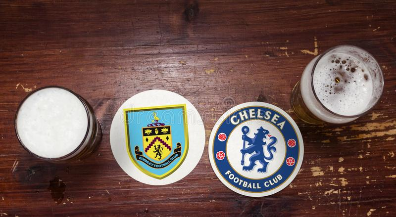 Burnley vs. Chelsea. Football team logos on beer mat at the pub with pints of beer royalty free stock photos