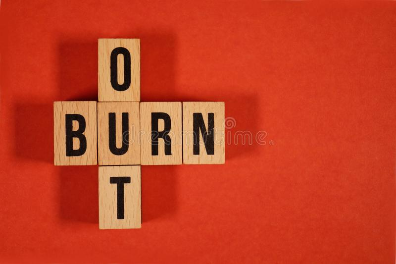 Burnout Word Written In Wooden Cube. Burn out, cube with letters. dice with text. concept of the destruction of shortcomings, fear. Burnout at work, daily stock photo
