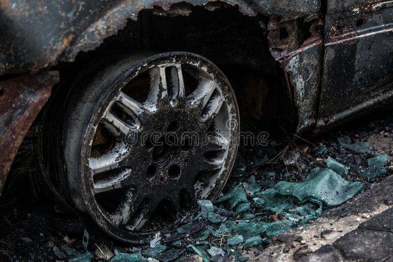 Burnt car on road. Burnt tire and molten glass. Car accident stock image