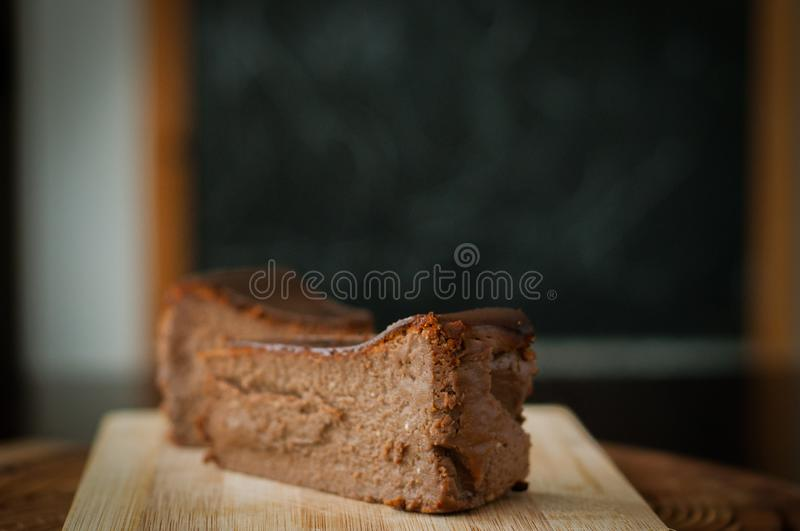 Burnt chocolate cheesecake on brown wooden background. Selective focus, appetizing, aromatic, bake, birthday, calorie, carbohydrates, celebrate, celebration royalty free stock photo