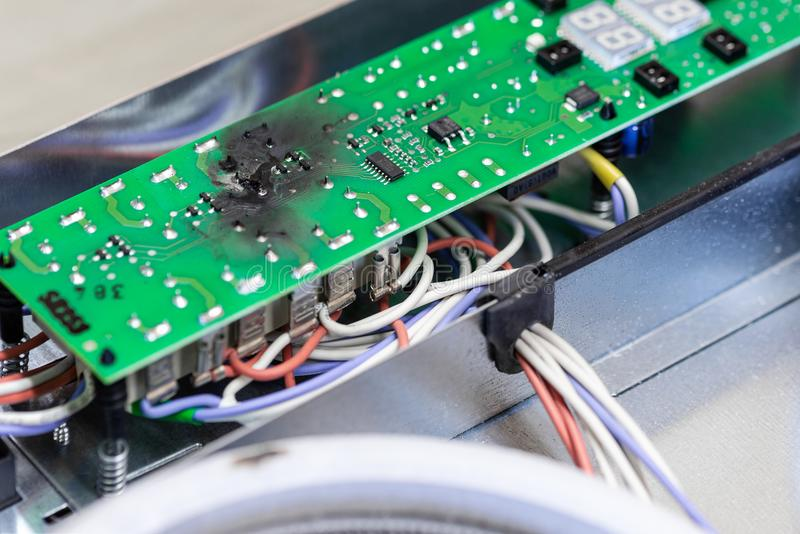 Burnt green microchip after short circuit due to water damage. Damaged overheat control panel board of cooking stove royalty free stock images