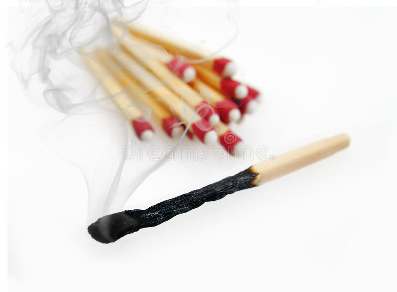 Burnt Match. A smoky, burnt match set aside from other matches. a Metaphor for burn out royalty free stock photo