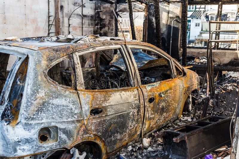 Burnt out car in a garage - police-secured crime scene - forbidden to enter royalty free stock photo