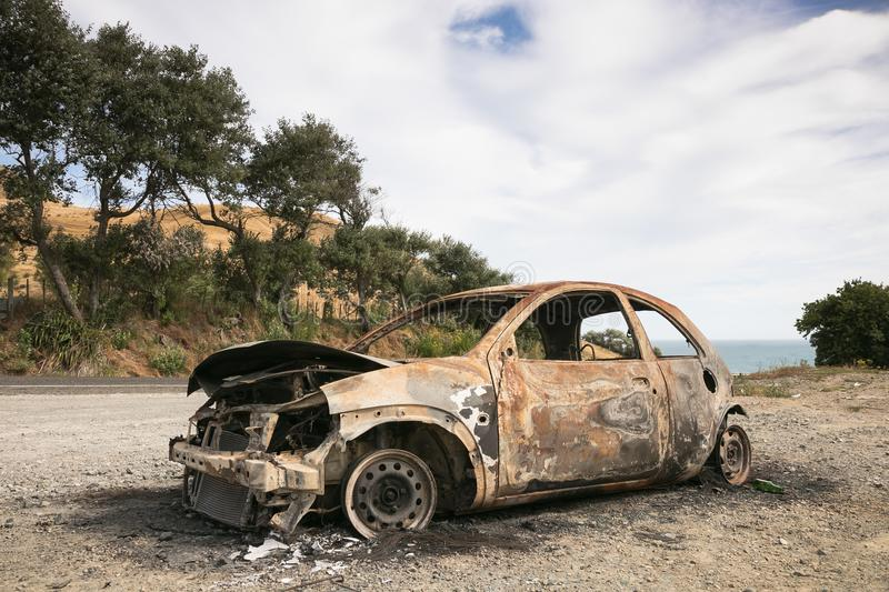 Burnt out car on the side of a road royalty free stock photo