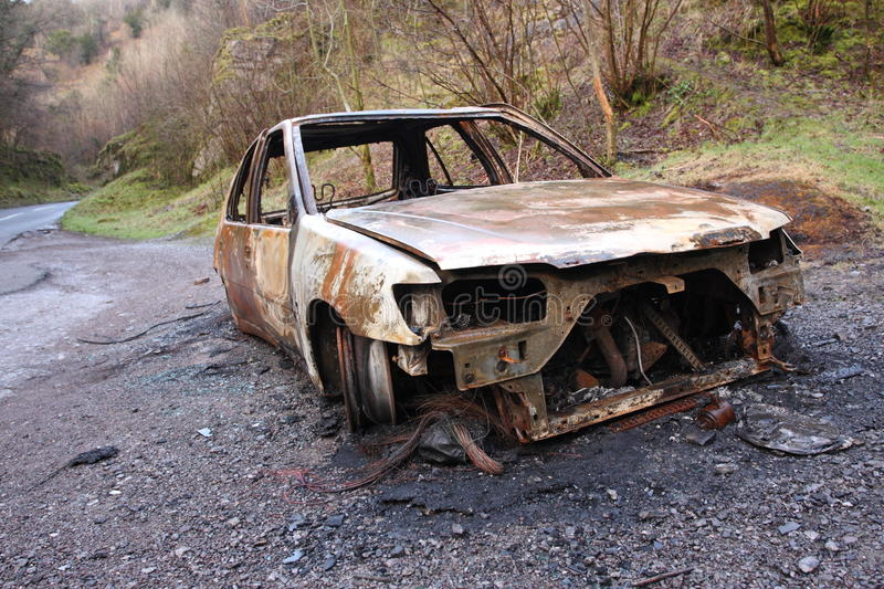 Burnt out car wreck on road stock photos