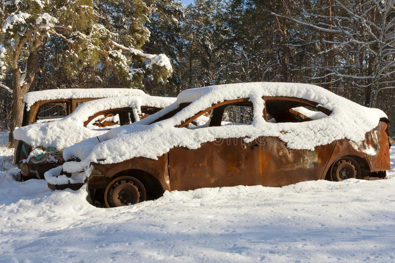 Burnt-out cars covered in snow stock image