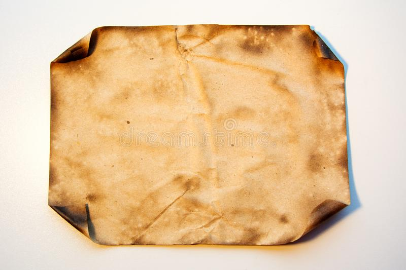 Burnt paper texture. Old crushed paper with the burned curved edges. royalty free stock images