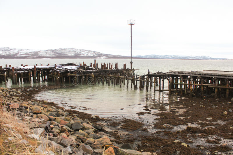 Burnt pier. The burnt pier in the Pechenga Bay stock photos