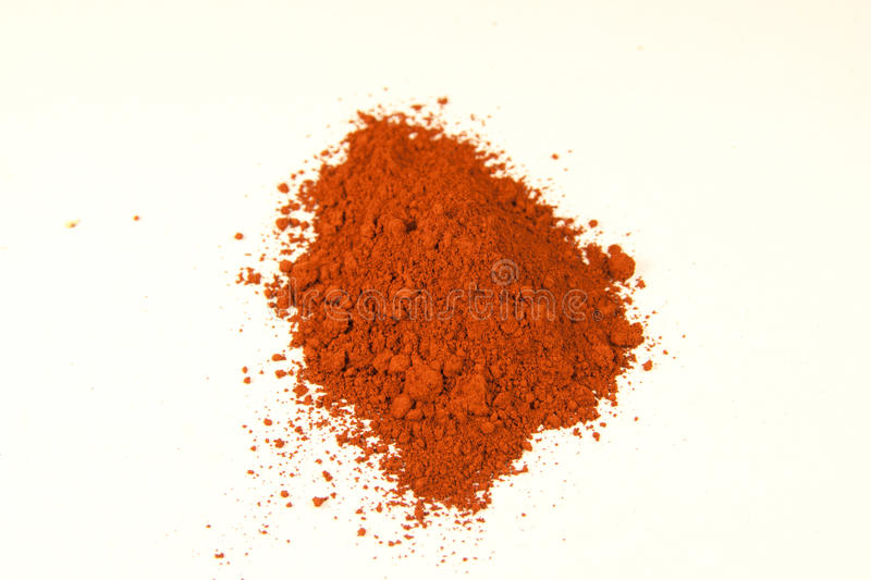 Burnt siena pigment. Close up of a small portion of red pigment over white stock images