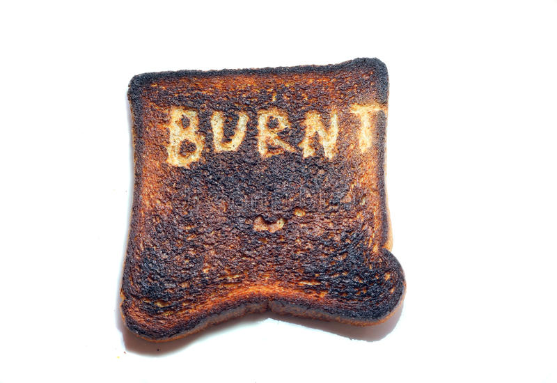 Burnt toast on a white background. A single piece of burnt toast on a white background with the word burnt scraped into it stock photo