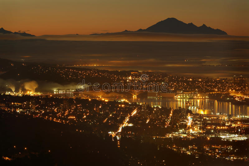 Burrard Inlet Twilight, Mount Baker, Vancouver. The view from the Cypress Mountain lookout of Vancouver and Burrard Inlet. The silhouette of Mount Baker in stock photo