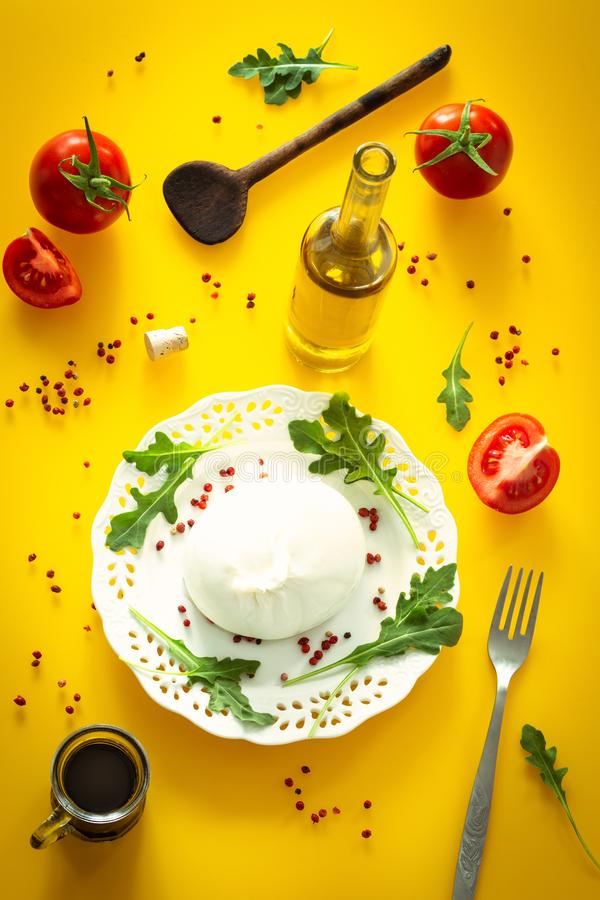 Burrata, Italian cheese with tomatoes, spices, argugula and olive oil and balsamic vinegar / yellow background stock photography