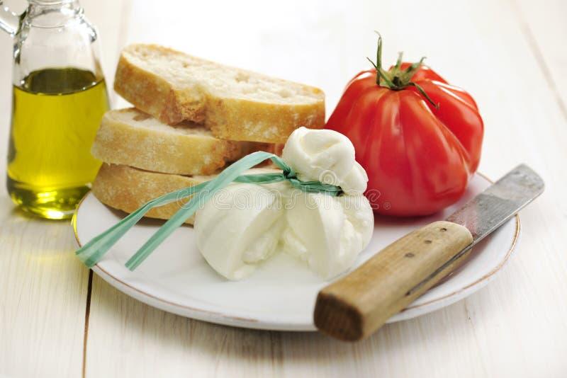 Burrata, tomato and bread royalty free stock photography
