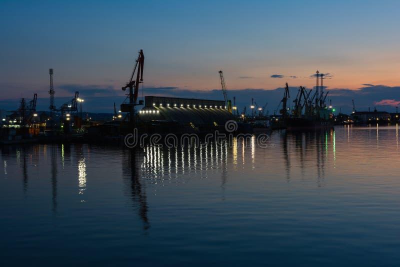 Burrgas-Seehafen nachts Schattenbilder von Kränen und von Reflexionen im Wasser stockbild