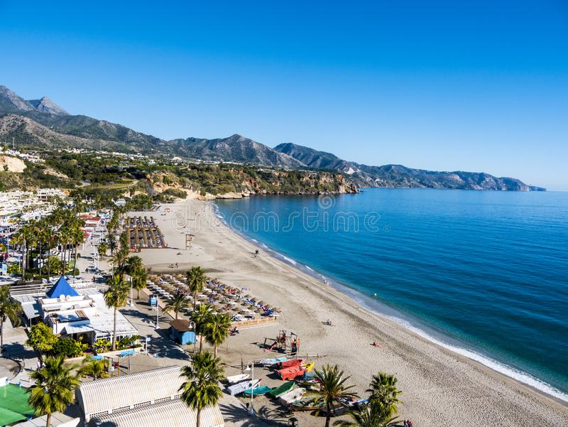 Burriana beach in the Spanish Town of Nerja in Andalucia. Nerja, on the Costa del Sol, Spain is a seaside resort of sandy coves sheltered by the impressive stock photography